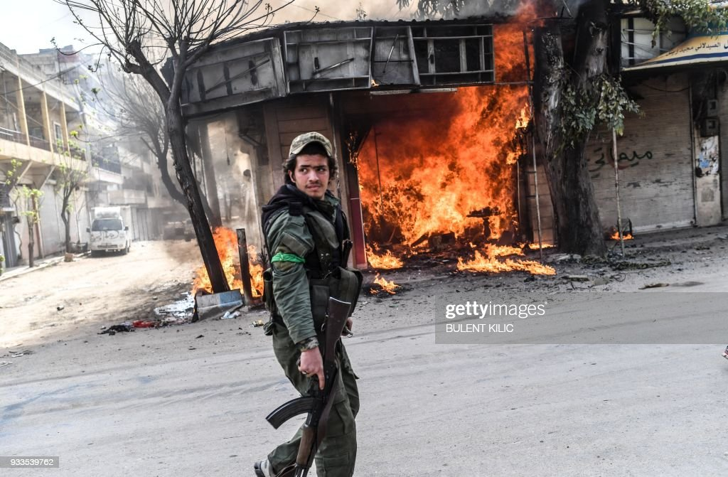 A Turkish-backed Syrian rebel walks past a burning shop in the city of Afrin in northern Syria on March 18, 2018. Turkish forces and their rebel allies were in control of the Kurdish-majority city of Afrin in northwestern Syria, AFP journalists on the ground reported. KILIC