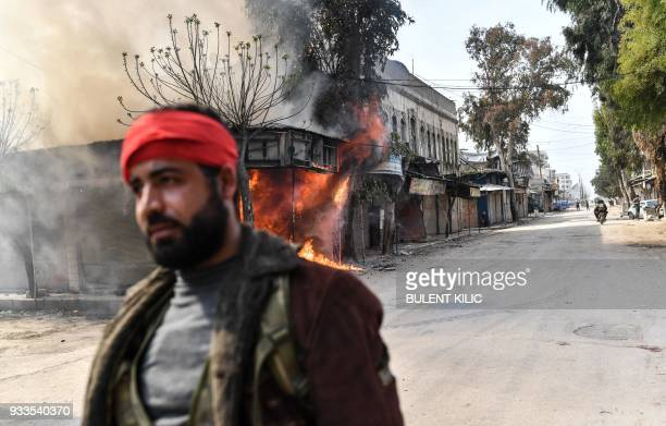 Turkishbacked Syrian rebel walks past a burning shop in the city of Afrin in northern Syria on March 18 2018 Turkish forces and their rebel allies...