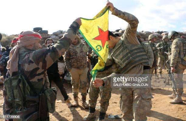 Turkishbacked Syrian rebels and soldiers prepare to burn the Kurdish People's Protection Units flag at Mount Barsaya on the SyrianTurkish border...