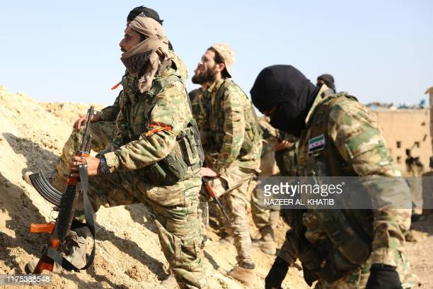 Turkishbacked Syrian rebels and Turkish soldiers watch as smoke billows from the border town of Ras alAin on October 12 as Turkey and its allies...
