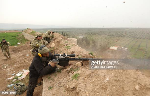 TOPSHOT Turkishbacked Syrian rebels fight Kurdish forces on the outskirts of the town of Jandairis on March 8 2018 in Syria's Afrin region near the...