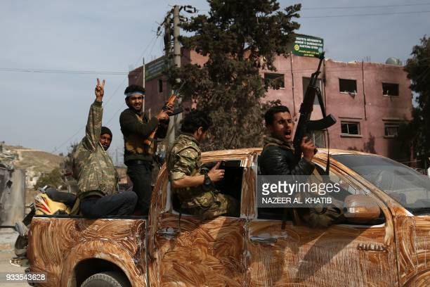 TOPSHOT Turkishbacked Syrian rebels gather in the city of Afrin in northern Syria on March 18 2018 Turkishbacked rebels have seized the centre of...