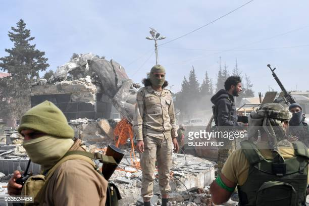 Turkishbacked Syrian rebels gather next to the destroyed statue of 'Kawa' the blacksmith who was a central figure in a Kurdish legend about the new...