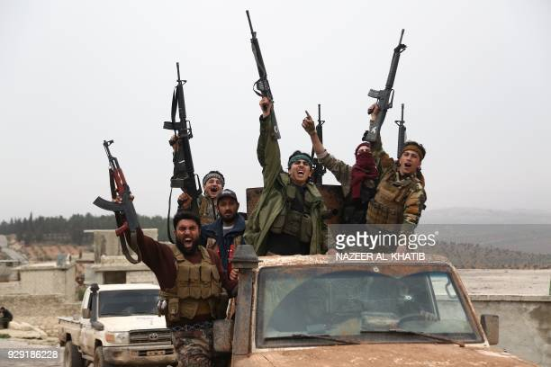 TOPSHOT Turkishbacked Syrian rebels gesture as they drive down a road in the area of Hallubi north of Afrin on March 8 2018 / AFP PHOTO / Nazeer...