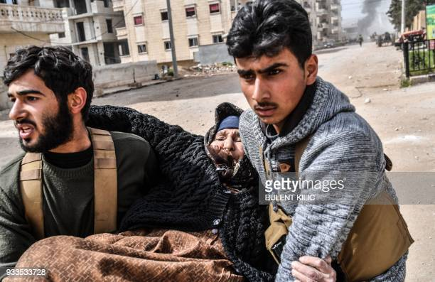 TOPSHOT Turkishbacked Syrian rebels help evacuate an elderly woman following explosions in the city of Afrin in northern Syria on March 18 after...