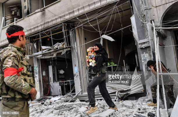 TOPSHOT Turkishbacked Syrian rebels loot shops after seizing control of the northwestern Syrian city of Afrin from the Kurdish People's Protection...