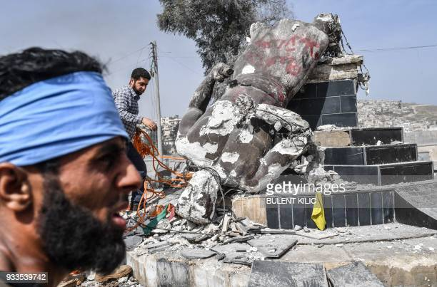 Turkishbacked Syrian rebels remove a rope from the statue of 'Kawa' the blacksmith who was a central figure in a Kurdish legend about the new year...