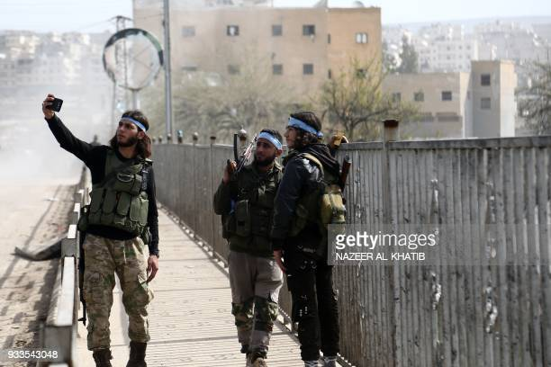 TOPSHOT Turkishbacked Syrian rebels take a picture as they gather in the city of Afrin in northern Syria on March 18 2018 Turkishbacked rebels have...