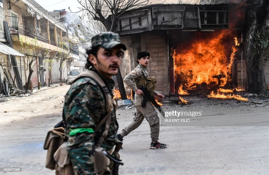 Turkish-backed Syrian rebels walk past a burning shop in the city of Afrin in northern Syria on March 18, 2018. Turkish forces and their rebel allies were in control of the Kurdish-majority city of Afrin in northwestern Syria, AFP journalists on the ground reported. PHOTO / Bulent Kilic