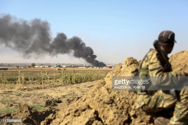 Turkishbacked Syrian rebels watch as smoke billows from the border town of Ras alAin on October 12 as Turkey and its allies continued their assault...