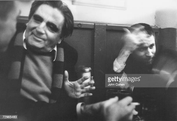 Turkishborn Greek American artist Aristodimos Kaldis and American painter Allan Kaprow gesture as they talk to two other people at a table in Cedar...