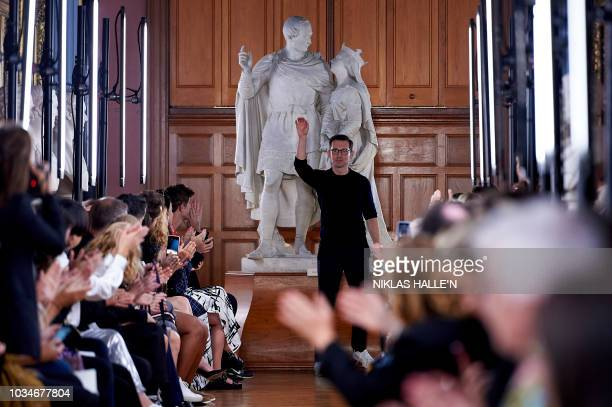 TurkishCanadian designer Erdem Moralioglu receives applause after presenting his creations during a catwalk show for the Spring/Summer 2019...