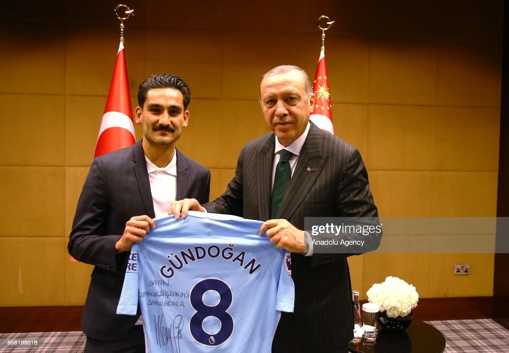 Turkish-German football player Ilkay Gundogan who plays for Manchester City (L) presents a jersey to Turkish President Recep Tayyip Erdogan before their meeting in London, United Kingdom on May 13, 2018.