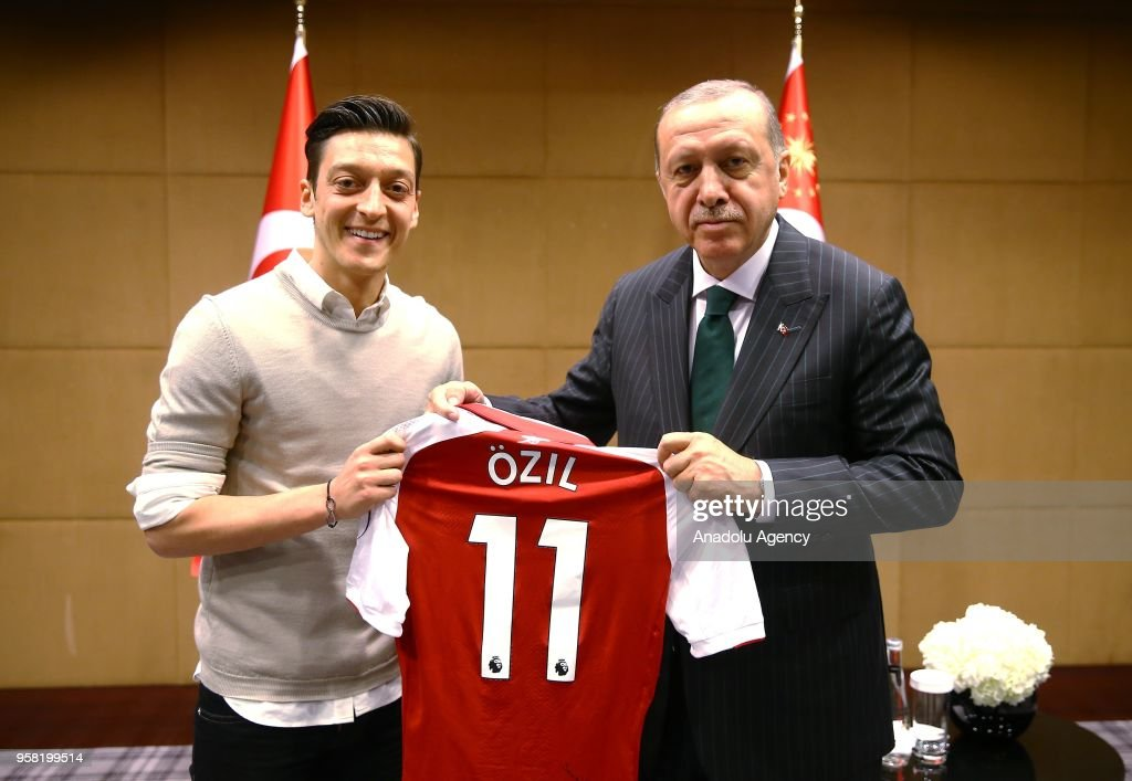 Turkish-German football player Mesut Ozil who plays for Arsenal (L) presents a jersey to Turkish President Recep Tayyip Erdogan before their meeting in London, United Kingdom on May 13, 2018.