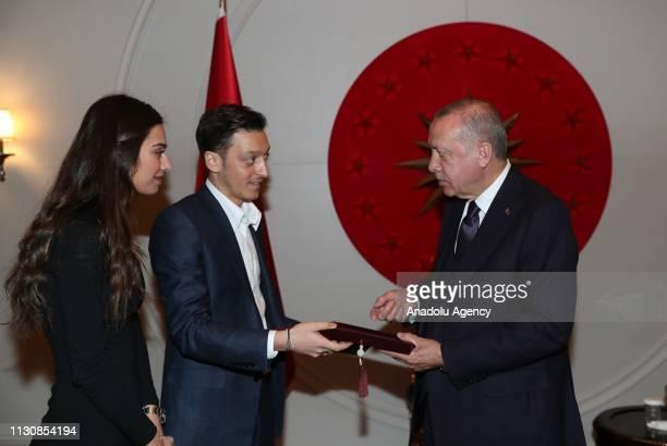 TurkishGerman footballer Mesut Ozil and his fiancee Amine Gulse present their wedding invitation to President of Turkey Recep Tayyip Erdogan as...