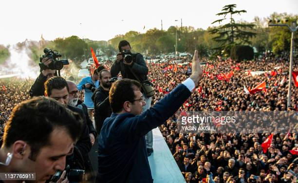 Turkisih main opposition Republican People's Party newly elected Istanbul mayor Ekrem Imamoglu waves to supporters gathered outside the city hall...