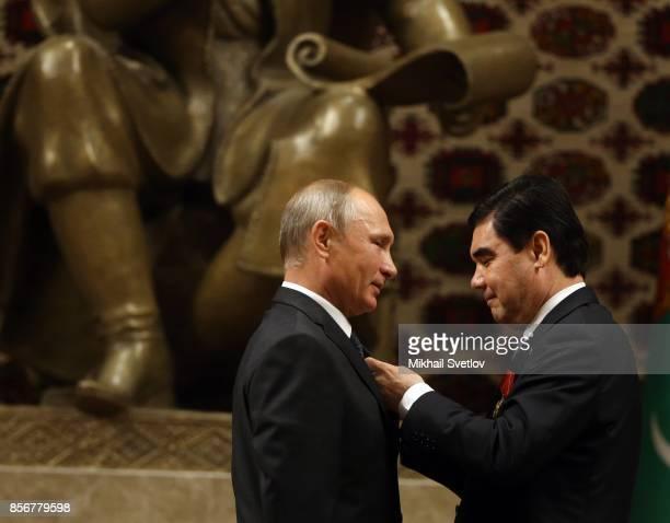 Turkmen President Gurbanguly Berdimuhamedow gives an order to Russian President Vladimir Putin during their meeting October 2 2017 in Ashgabad...