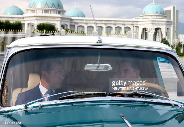 Turkmen President Gurbanguly Berdymukhamedov and Russian Prime Minister Dmitry Medvedev ride in a GAZ-21 Volga car during a meeting in Ashgabat on...
