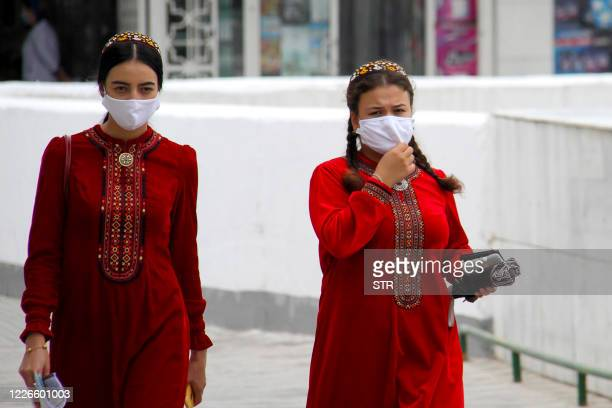 Turkmen women wearing face masks walk in Ashgabat on July 13, 2020. - Reclusive Turkmenistan on July 13 recommended that residents wear masks because...