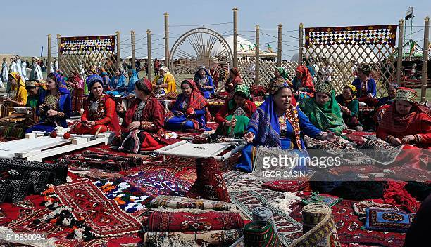 Turkmen women wearing traditional costumes craft hand made carpets during the celebrations of Nowruz outside Turkmenistan's capital Ashgabat, on...