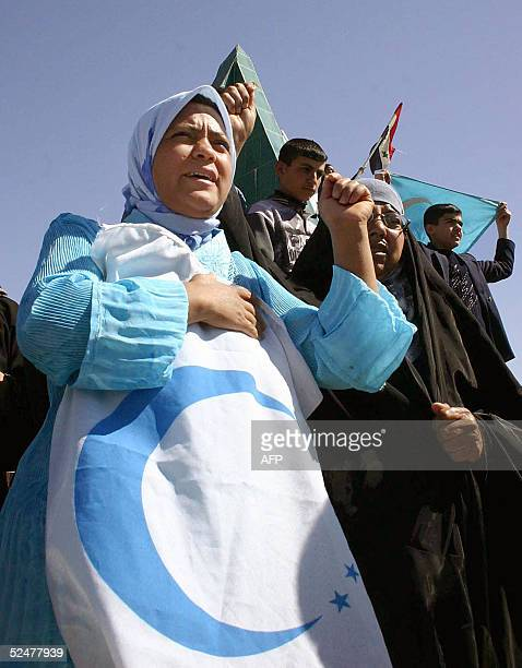 Turkmen women with the Turkmen flag protest in the northern city of Kirkuk 25 March 2005. The Turkmen community demanded that US troops release their...
