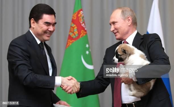 Turkmenistan's President Gurbanguly Berdymukhamedov shakes hands with Russian President Vladimir Putin after presenting him a Turkmen shepherd dog,...