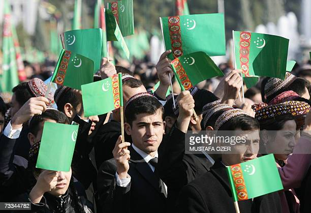 Turkmens hold Turkmenistan flags as they attend a newly-elected President Gurbanguly Berdymukhammedov's oath ceremony 14 February 2007 in Ashgabat,...