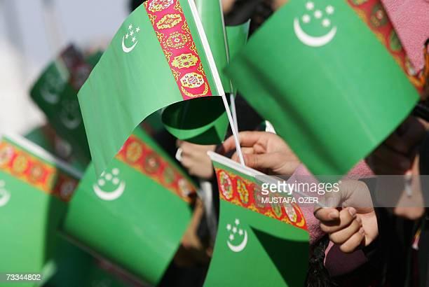 Turkmens hold Turkmenistan flags as they attend a newlyelected President Gurbanguly Berdymukhammedov's oath ceremony 14 February 2007 in Ashgabat...