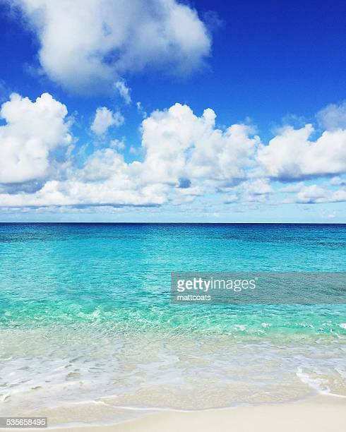 turks and caicos islands, white clouds above clear shallow sea - turks and caicos islands stock pictures, royalty-free photos & images