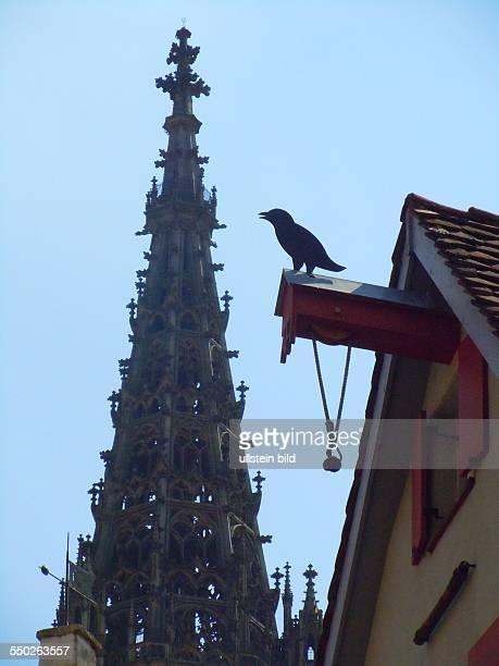 Turm des Münsters und eine Rabenfigur auf dem historischen Lastenaufzug eines Kaufmannshauses aufgenommen in Ulm am 17 Juli 2013