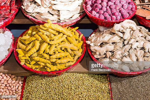 Turmeric ginger caraway seeds and peanuts are displayed in bowls in the Old Delhi spice market
