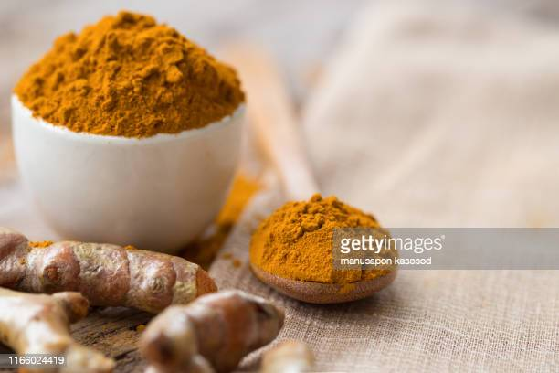 turmeric powder and fresh turmeric in wood bowls on wooden table. - ginger spice stock pictures, royalty-free photos & images