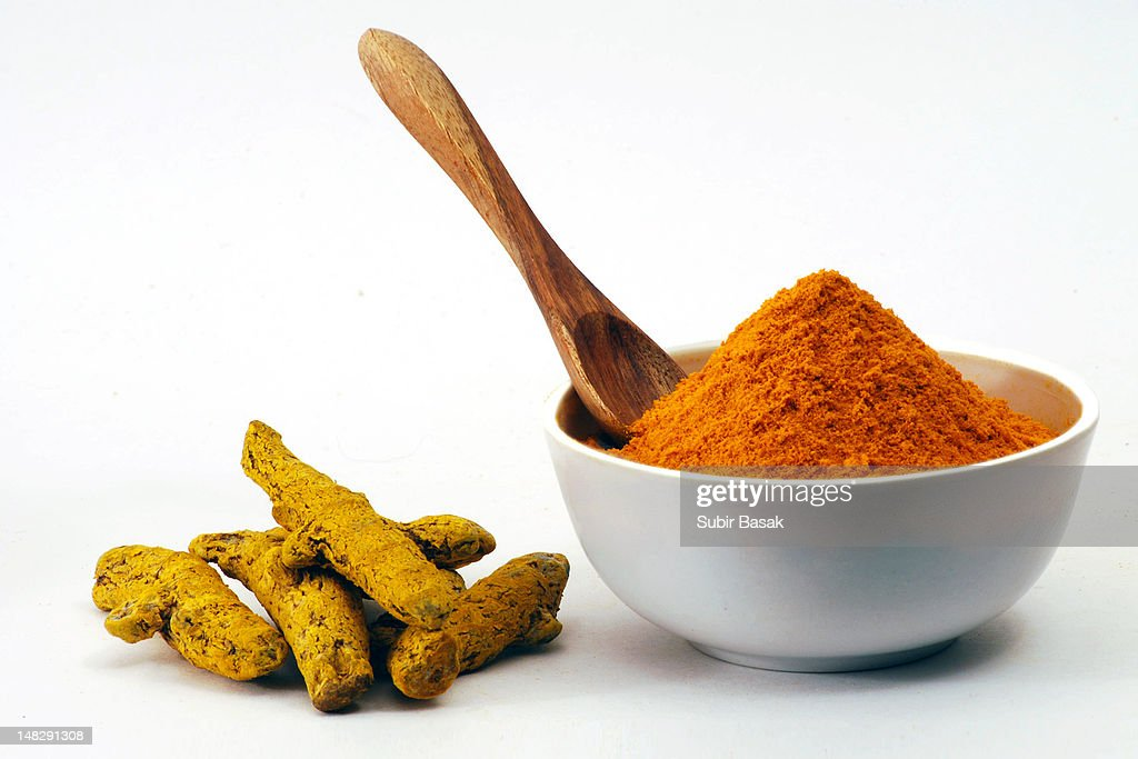 Turmeric powder in bowl and raw turmeric : Stock Photo