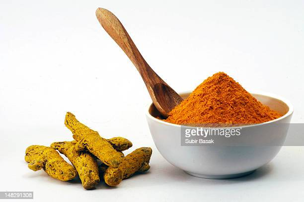 Turmeric powder in bowl and raw turmeric