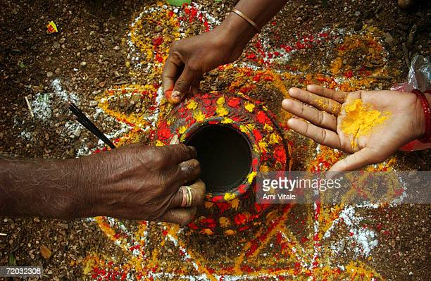 Turmeric powder is applied to a pot that will be used in a 'puja' ceremony to worship the goddess Yellama August 19 2005 in Andrha Pradesh India...