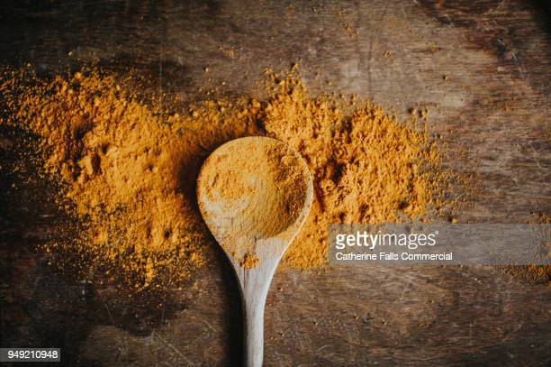 turmeric powder on a wooden spoon - curry stock pictures, royalty-free photos & images