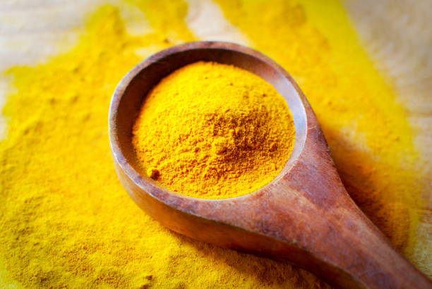 turmeric powder - wooden spoon - turmeric stock pictures, royalty-free photos & images