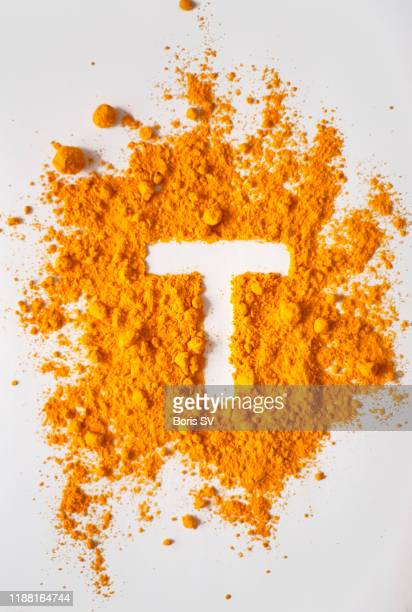 turmeric powerd forming letter t - letter t stock pictures, royalty-free photos & images