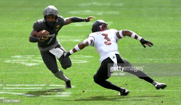 Turner of the Pittsburgh Panthers runs upfield after a catch as Russ Yeast of the Louisville Cardinals defends in the first quarter during the game...