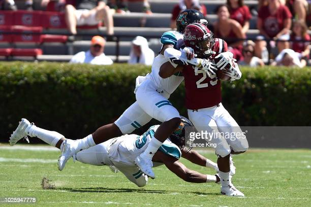 J Turner of the South Carolina Gamecocks tries to avoid a tackle by Laqavious Paul and Ryan Lee of the Coastal Carolina Chanticleers at WilliamsBrice...