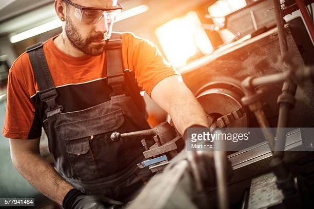 Turner worker working on drill bit in a workshop