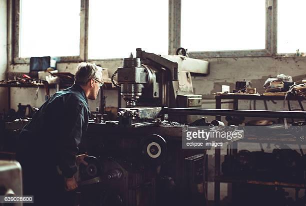 Tornero obrero trabajando con broca en un taller