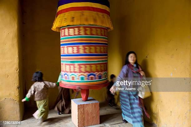 turning large prayer wheel, punakha dzong at the convergence of two rivers mo chhu and pho chhu, punakha, bhutan - プナカ ストックフォトと画像