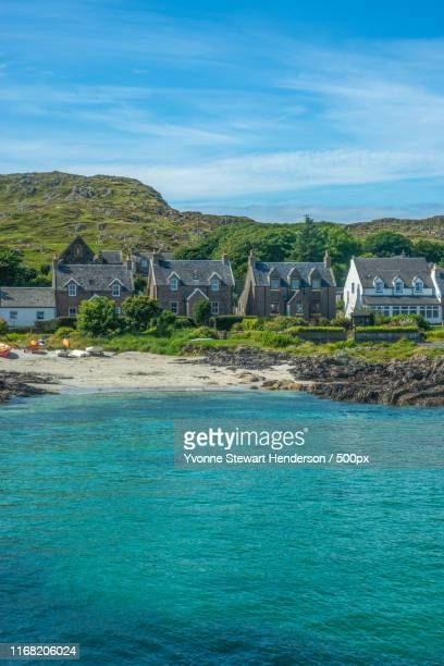 turquoise bay with traditional cottages by the beach on the isle - barra scotland stock pictures, royalty-free photos & images