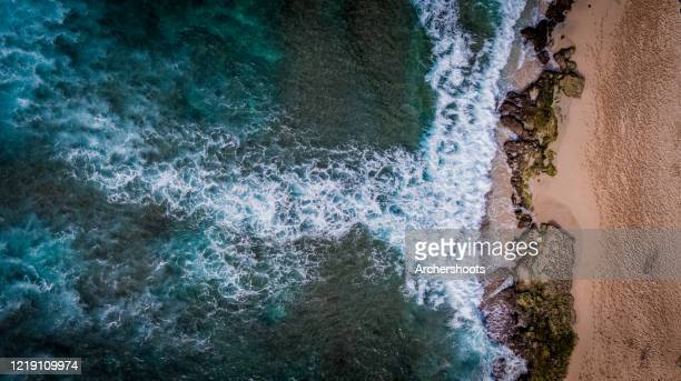turquoise blue ocean coastline along red sand beach - reef stock pictures, royalty-free photos & images