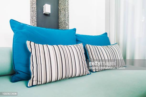 turquoise colored bed with blue pillows against curtain in bedroom - cushion stock photos and pictures