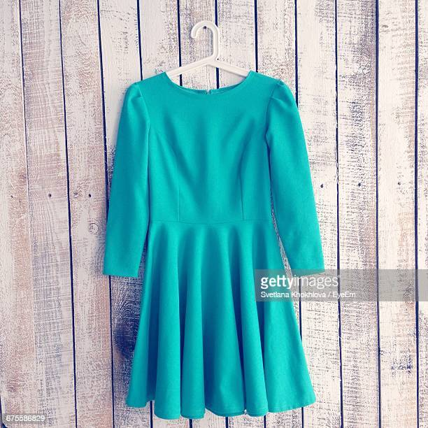 Turquoise Dress Hanging From Wooden Wall