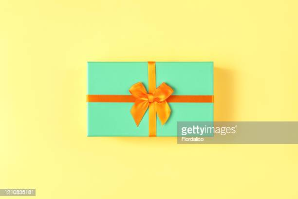 turquoise gift box with orange ribbon tied in a beautiful bow on pastel yellow background - gifts stock pictures, royalty-free photos & images