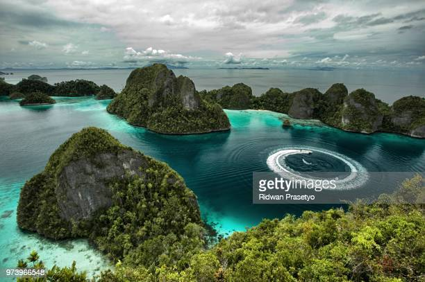 turquoise lagoon among rocks under cloudy sky, wayag island, raja ampat, west papua, indonesia - raja ampat islands stock photos and pictures
