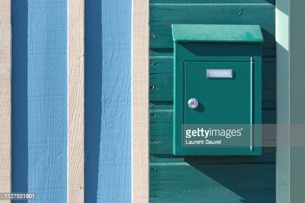 a turquoise mailbox on a turquoise, white and light blue painted wooden wall - mailbox stock pictures, royalty-free photos & images